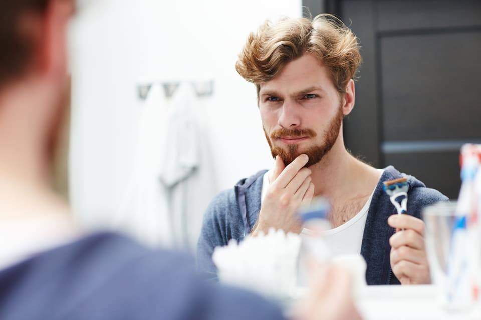 man preparing to shave his beard off