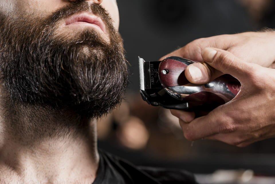 man having his beard trimmed